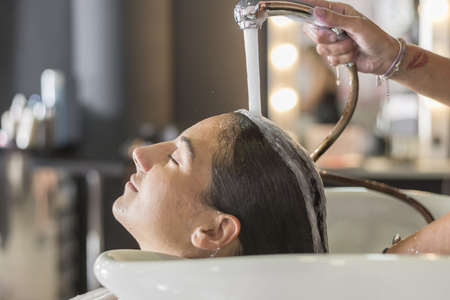Young woman washing hair in salon ( hairdresser concept )