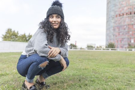 portrait of a woman with wool cap and sweater crouched on a grass garden
