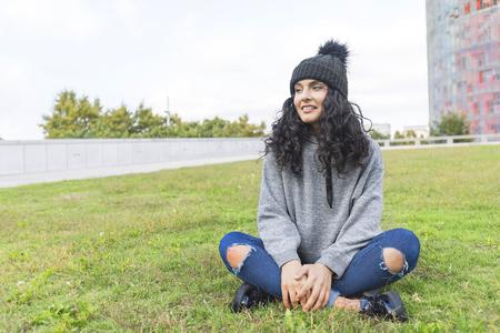Portrait d & # 39 ; une femme avec bonnet de laine et pull assis sur un jardin d & # 39 ; herbe Banque d'images - 94230691