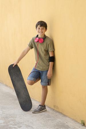 A Teen with skateboard on the city street ( Headphone around neck ) Stock Photo