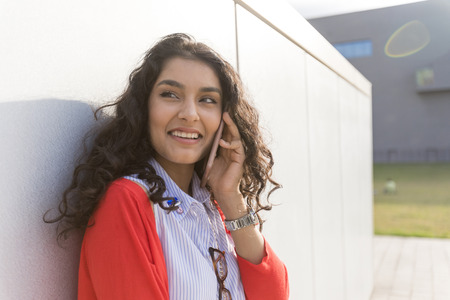 Woman calling on phone standing next to a  wall wearing red jacket
