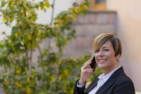 Smilie executive talking on phone looking at camera on the street