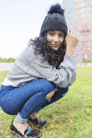 retrato de una mujer con gorro de lana y suéter acurrucado en un jardín de hierba
