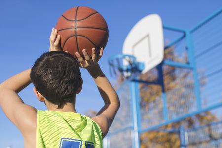 adolescente lanzando un baloncesto en el aro desde arriba