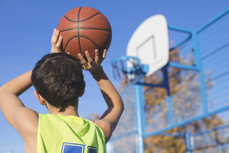 teenager throwing a basketball into the hoop from behind