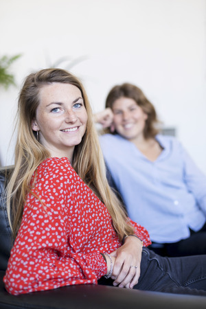 Two friends talking and laughing sitting on a sofa in the living room at home