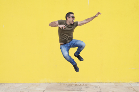 Young man with sunglasses jumping in front of a yellow wall ( freedom )