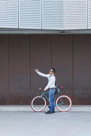 Hipster man taking a selfie . He is commuting, he has a fixed gear bike. Lifestyle, travel and sustainability concepts. Фото со стока