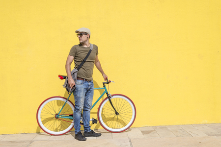 Man posing with his fixed gear bicycle wearing sunglasses