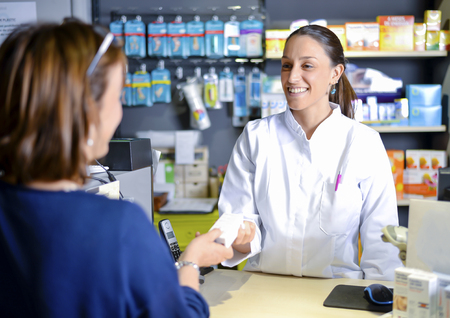Female pharmacist staff counseling customer about drugs usage in modern pharmacy