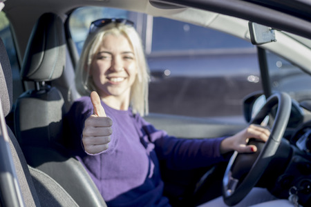 Beautiful woman inside a car showing thumbs up