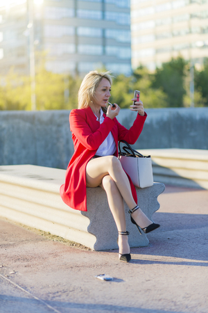 Trendy blonde woman using her lipstick sitting on a bench and using the smartphone as a mirror Фото со стока