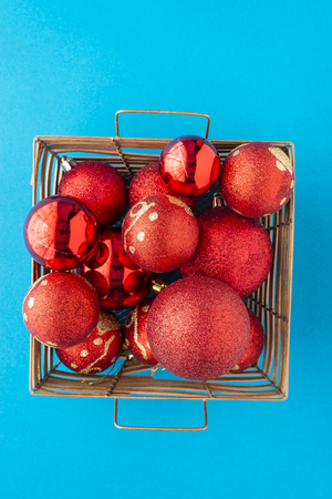 A multitude of red christmas globes together in a gold basket on a blue background