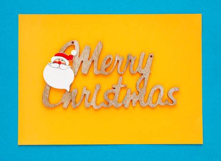 View from above of a Merry Christmas inscription on colored background, greeting card with space for text writing