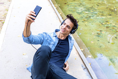Happy attractive young man in headset taking selfie on his mobile phone. Dressed in jeans shirt