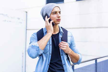 Young man holding mobile phone, using smartphone, making a call, talking on the phone