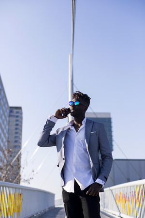 Front view of a smiling young black african man wearing elegant clothes standing in the street while using a mobile phone outdoors in sunny day