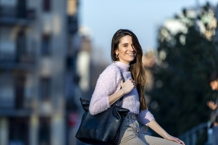 Front view of a beautiful trendy young woman smiling and wearing casual wear sitting on a metallic fence in the street while looking camera in a sunny day Reklamní fotografie
