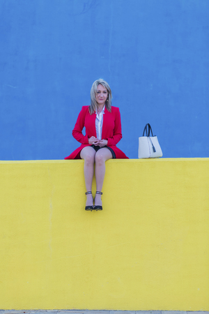 Low angle view of an elegant blonde woman in red jacket sitting on a bench outdoors while looking camera in sunny day
