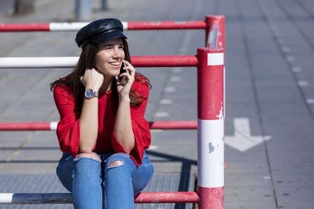 Front view of beautiful young woman wearing urban clothes sitting on a metallic fence while using a mobile phone outdoors in the street in a bright day