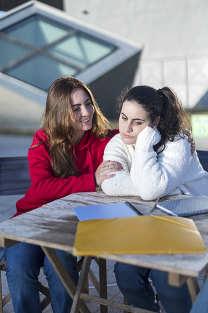 Desperate student woman getting support from a best friend sitting outdoors