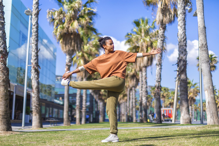 Black woman, afro hairstyle, doing yoga asana in promenade Imagens