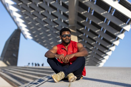 Front view of young black man wearing sunglasses sitting on staircase in a sunny day while looking away