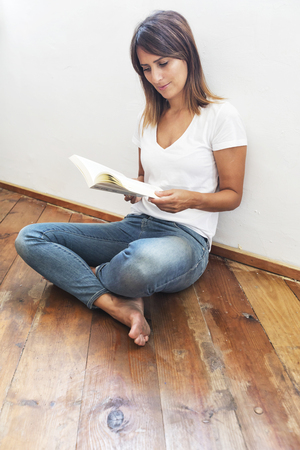 Beautiful woman sitting on ground leaning on a white wall while reading a book