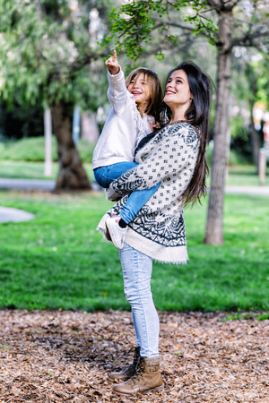 Mom holding her daughter and playing around the park on beautiful morning