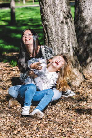Mother and little daughter enjoying together while sitting in the park in a bright day Stock Photo