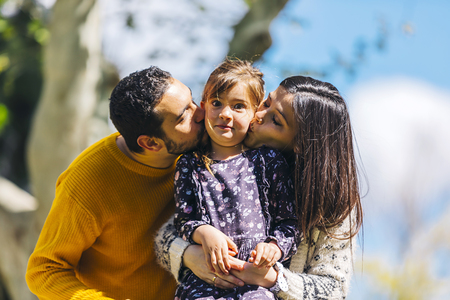 Front view of a happy parents kissing her lovely daughter outdoors in the park in a sunny day