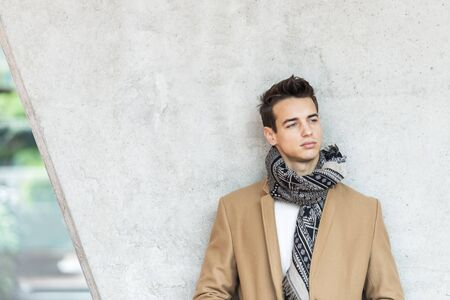 Front view stylish young man wearing coat and scarf leaning on a wall while looking away