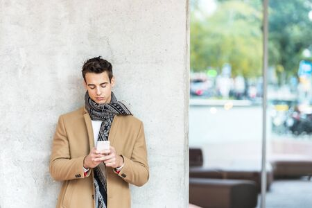 Young man writing phone message. Mid adult man typing on mobile while standing on grey background. Man leaning on gray wall while browsing internet on smartphone Imagens