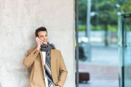 Young man calling. Mid adult man using a mobile phone while standing on grey background. Man leaning on gray wall while looking away and smiling outdoors