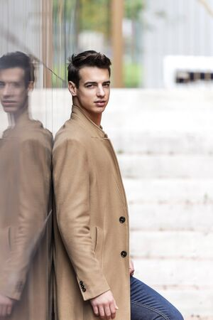 Young man with coat leaning on a reflective wall while looking away on the street Imagens