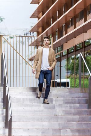 A young man descends by the stairs in the city wearing a coat.Fashionable dressed guy. Life style Imagens