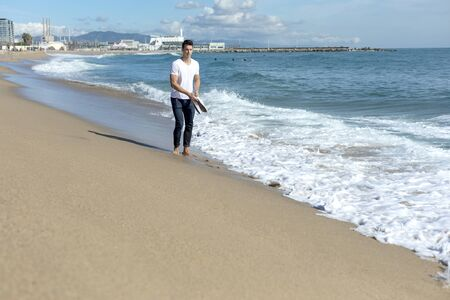 Young man walking on seashore holding a pair of sneakers in a sunny day