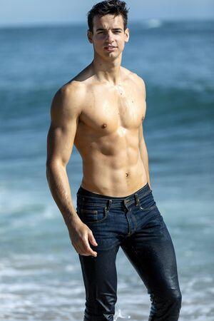 Hombre musculoso atractivo joven en la orilla del mar en un día soleado Foto de archivo