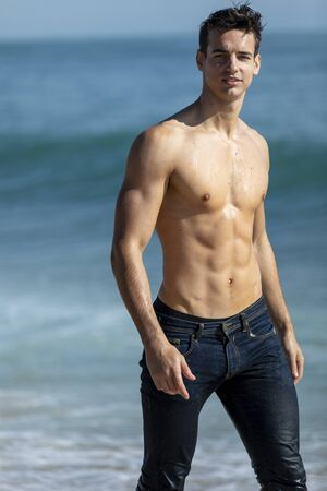 Young attractive muscular man on seashore in a sunny day Imagens
