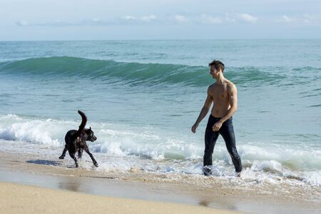 young caucasian male playing with dog on beach during sunrise or sunset. Man and dog having fun on seaside