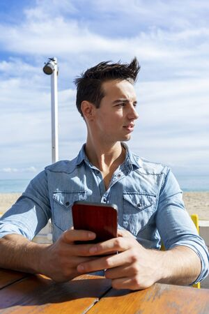 Front view of young man sitting on beach club while using a mobile phone in a sunny day