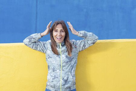 Just happy. Young smiling exited woman in casual wear holding hands on head and shouting while standing against yellow wall background. Cheerful crazy girl with open mouth posing to camera