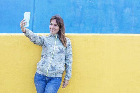 One happy young woman taking selfie outdoors against a yellow and blue wall Imagens