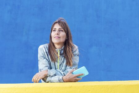 Casual adult woman lean on yellow wall holding a mobile phone while looking away outdoors