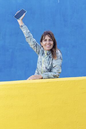Beautiful woman lean on yellow wall looking camera while holding a mobile phone up in the air Imagens