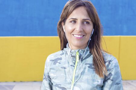 Close up portrait of happy woman smiling with headphones outside