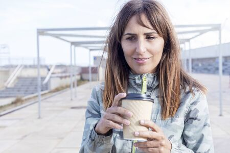 Pretty young woman in casual wear holding take away cup in hands. Drinking take away coffee. Breakfast on the go.