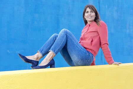 Beautiful adult woman in jeans lying on a yellow fence while looking away against blue wall background Imagens