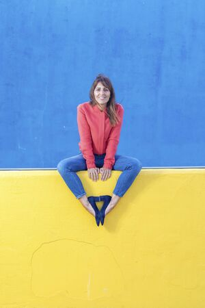 Beautiful adult woman in jeans sitting on a yellow fence while looking camera against blue wall background