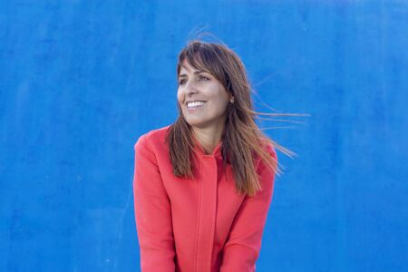 Woman with white teeth thinking and looking sideways against a blue wall background.
